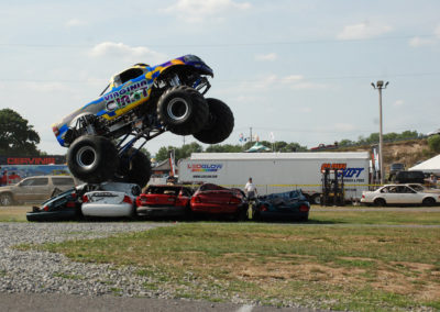 the virginia giant monster truck at the 2011 truck nationals crushing cars while doing a wheelie