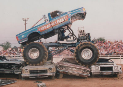 The original virginia giant monster truck sitting on cars and opened up