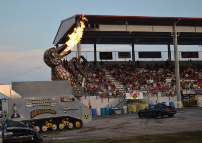 2012 Carlisle Truck Nationals with people in stands and megasaurus with fire coming out of its mouth