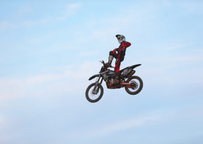 motorcycle in air with rider doing stunts