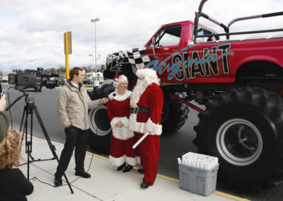 Virginia giant truck with santa and Mrs. Claus standing in front of truck being interviewed.
